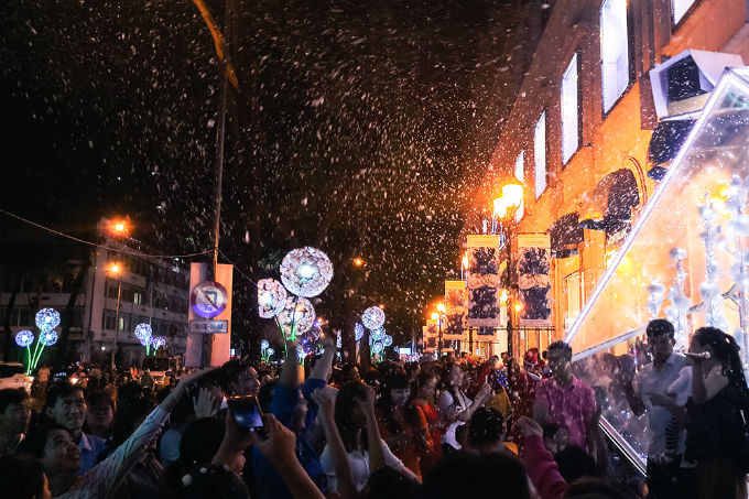 People gather in front of a shopping center in District 1 to play with fake snow coming from a machine.