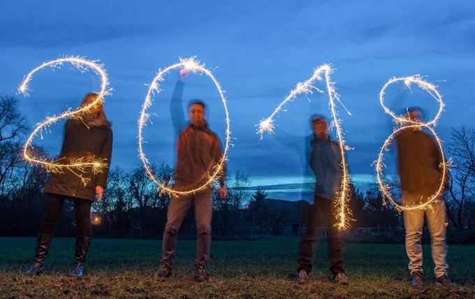Illustration taken with a long time exposure on December 27, 2017 in Sieversdorf, eastern Germany, shows four people drawing the year 2018 with sparklers.Photo by AFP/DPA/Patrick Pleul