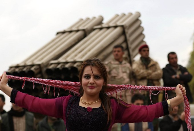 An Iraqi Kurdish woman dances as Peshmerga members gather to celebrate the New Year on the frontline in Makhmur, about 280 kilometres (175 miles) north of the capital Baghdad, on December 31, 2017.Photo by AFP/Safin Hamed
