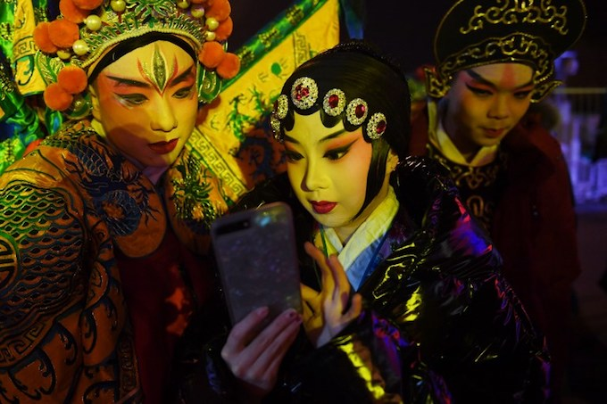 Performers look at selfie photos before going on stage at a countdown event marking the arrival of the New Year in Beijing on December 31, 2017.Photo by AFP/Greg BakerChildren pose for a photo before an ice sculpture depicting a Hwasong-15 intercontinental ballistic missile (ICBM) and self-propelled launcher, as people mark the new year at the Pyongyang Ice Sculpture Festival on Kim Il Sung Square in Pyongyang on December 31, 2017.Photo by AFP/Kim Won-Jin
