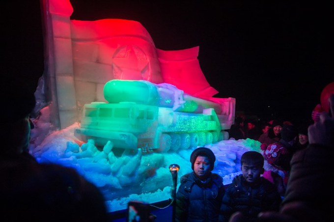 Children pose for a photo before an ice sculpture depicting a Hwasong-15 intercontinental ballistic missile (ICBM) and self-propelled launcher, as people mark the new year at the Pyongyang Ice Sculpture Festival on Kim Il Sung Square in Pyongyang on December 31, 2017.Photo by AFP/Kim Won-Jin