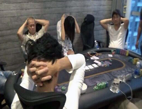 Players surrender during a police raid into an illegal casino in Saigon on Wednesday. Photo courtesy of the police