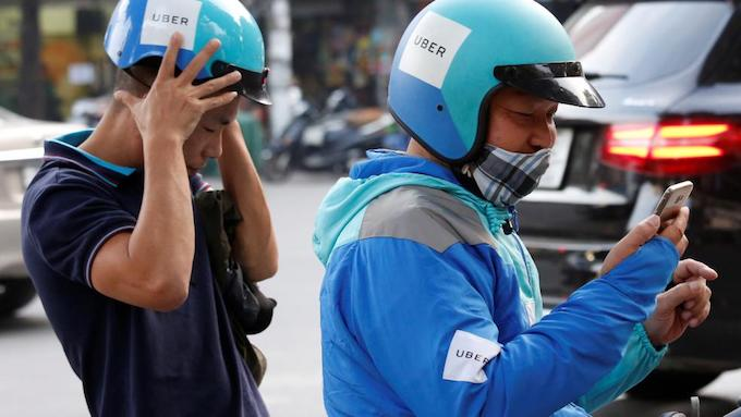 An Uber motorbike driver drops off his customer in Hanoi. Photo by Reuters