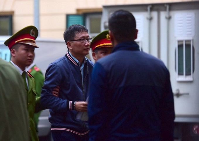 Trinh Xuan Thanh (C) is led by policemen to the courtroom at Hanoi Peoples Courthouse on January 8, 2018. Photo by AFP