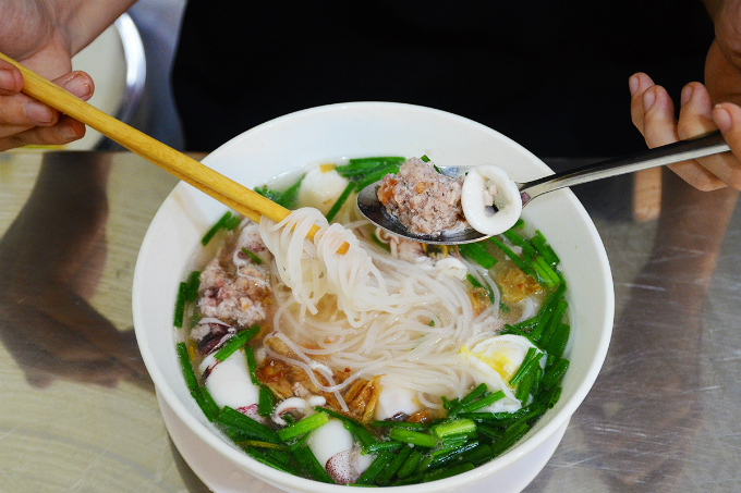 The restaurant serves hu tieu, a kind of rice-based noodles that is tough and translucent, with squids, meat balls, quail eggs, shrimps, and extra chivas and fried onions. A full bowl costs VND57,000 or $2.5.