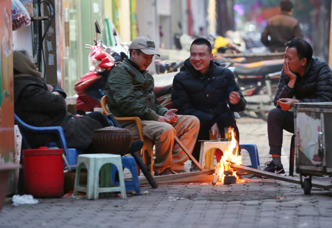 Men gather around a bonfire at a tea shop in the citys downtown. People do not mind if the sidewalks are taken over by some warmth.