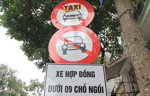 A sign banning contract cars under 9 seats beneath a sign banning taxis on a street in Hanoi. Photo by VnExpress/Anh Tu.