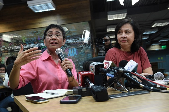 Maria Ressa (L), CEO, and editor of online portal Rappler, speaks during a press conference at their office in Manila on January 15, 2018, while acting managing editor Chay Hofilena (R) listens.Photo by AFP/Ted Aljibe