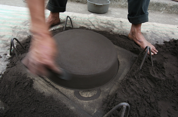 Dong uses a mold, sand and coal to make the pots.