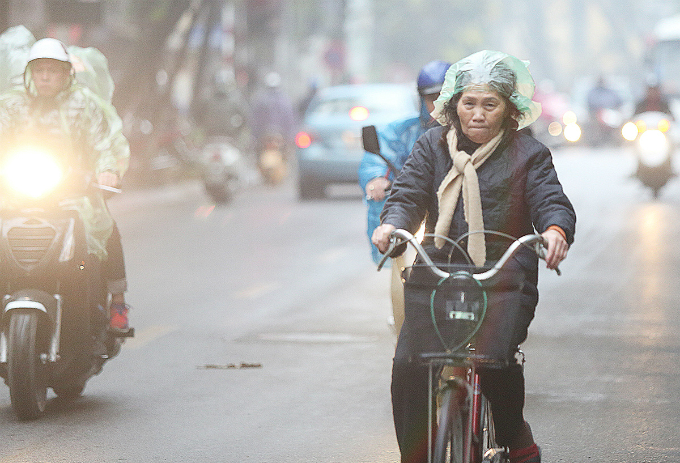 A woman covers her head with a plastic bag to keep her hair from getting wet.