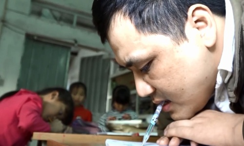 Disabled Hanoi teacher masters the art of calligraphy... with his mouth