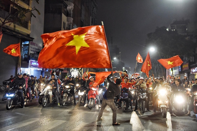 A fan waves the Vietnamese flag in the middle of Hang Bai Street in downtown Hanoi as other fans cheer on their motorbikes.