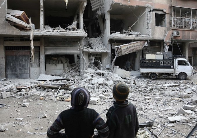 Syrian children look at a building that was damaged in a missile attack on the rebel-held besieged town of Arbin, in the eastern Ghouta region on the outskirts of the capital Damascus, on January 18, 2018. Photo by AFP/Abdulmonam Eassa