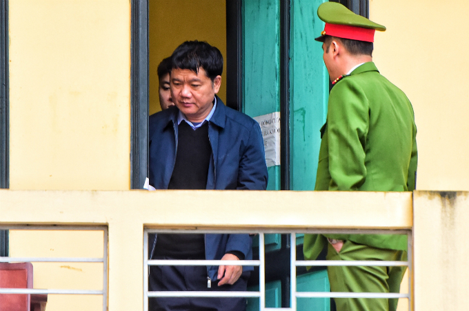 A police office stands guard as Dinh La Thang is taken to the PetroVietnam trial in Hanoi. Photo by Vietnam News Agency