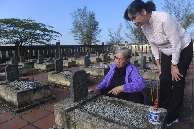 Nguyen Thi Hoa (L) and Hoang Thi No, who were members of the Perfurme River squad - a top secret female combat unit formed in 1967, look at a grave of a comrade killed during the 1968 Tet Offensive, on the outskirts of Hue. Photo by AFP/Hoang Dinh Nam