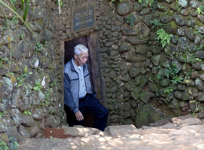 Nguyen Tri Phuong, who was amongst 250 local people involved in digging the Vinh Moc tunnel network, walks out from an entrance to the underground system, at the Vinh Moc commune in the central coastal province of Quang Tri. The Vinh Moc tunnels are among thousands of underground passageways built across Vietnam throughout the war, including the massive Cu Chi tunnels in Saigon, where Viet Cong guerrillas took shelter beneath the former Southern capital, which was renamed Ho Chi Minh city after the wars end in 1975. Photo by AFP/Hoang Dinh Nam