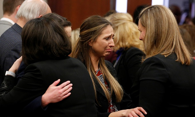 Prosecutor Angela Povilaitis (R) embraces victim Kyle Stephens (C) after the sentencing of Larry Nassar, a former team USA Gymnastics doctor who pleaded guilty in November 2017 to sexual assault charges, in Lansing, Michigan, U.S., January 24, 2018. Photo by Reuters/Brendan McDermid