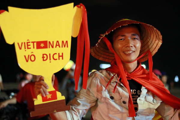 And in central resort town Nha Trang, a fan holds a paper cup reading Victorious Vietnam. Photo by VnExpress/Xuan Ngoc
