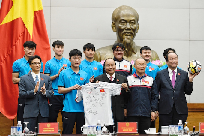 The Vietnam U23 football team poses for a photo with, second row, left to right, Deputy PM Vu Duc Dam, U23 team captain Luong Xuan Truong, PM Nguyen Xuan Phuc, coach Park Hang-seo and head of the Government Office Mai Tien Dung