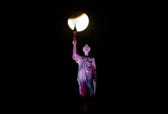 A lunar eclipse of a full blue moon is seen above a statue at the Chhatrapati Shivaji Terminus railway station in Mumbai, India. Photo by Reuters/Danish SiddiquiCaption]