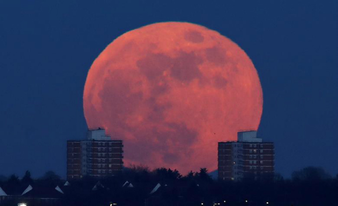 A full moon rises behind blocks of flats in north London.Photo by Reuters/Eddie Keogh