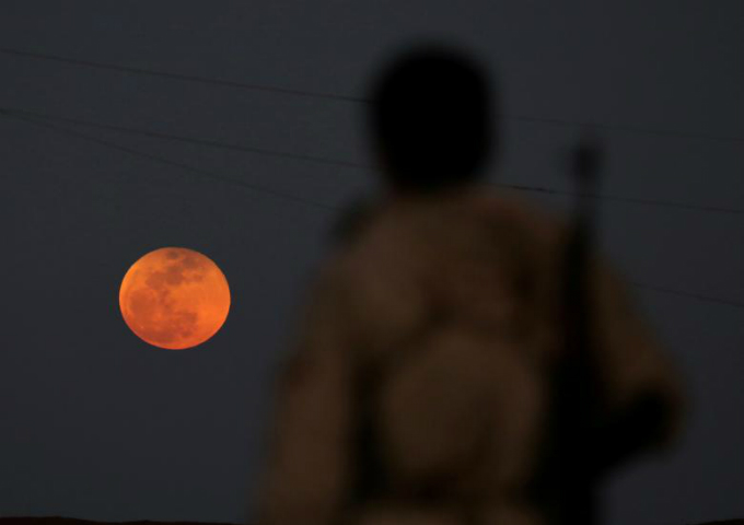 A fighter from Free Syrian Army is seen watching a full moon rises in Daraa, Syria. Photo by Reuters/Alaa al-Faqir