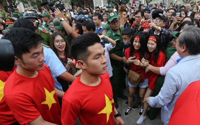 Fans approach as players of Vietnams U23 national football team walk from their bus to Nguyen Hue Pedestrian Street to pay tribute to late President Ho Chi Minh at his mausoleum.