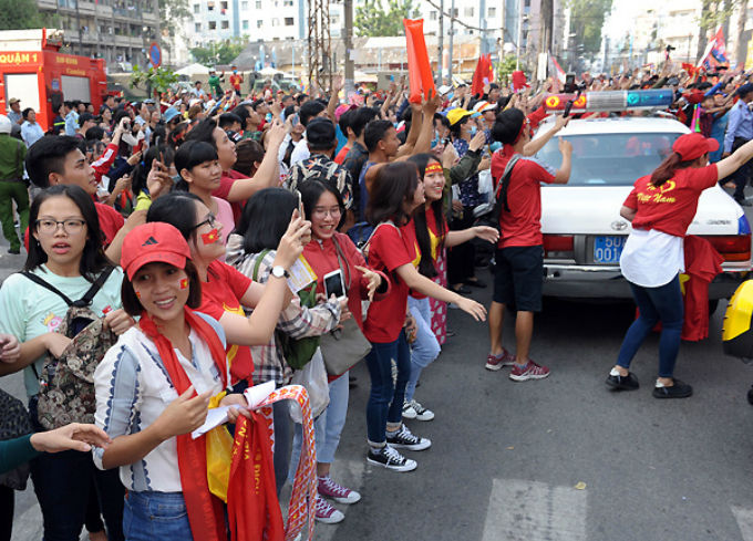 Fans wave outside Thong Nhat Statdium as the bus of U23 Vietnam approaches.