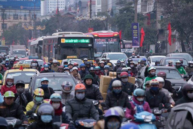Buses carry migrants out of the capital city on Wednesday afternoon as porters deliver holiday items and everyone are in a rush to complete other errands by year end. The Lunar New Year, or Tet, is coming in a week and the holiday fever is making Hanois already bad traffic even more terrible.