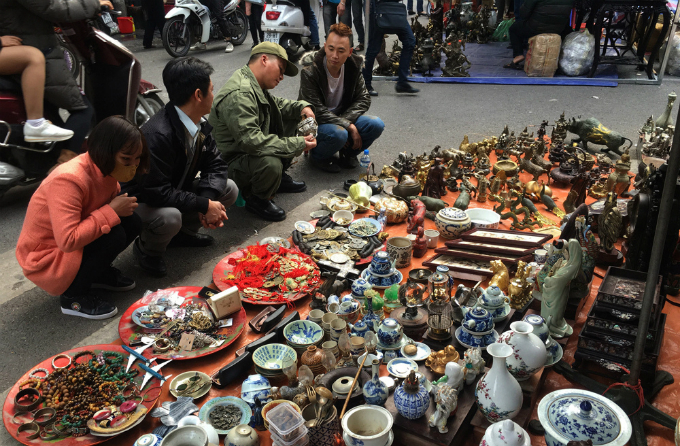 People check old items at the antiques market on Hang Ma Street, Hanoi. Photo by VnExpress/Vy An