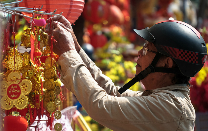 A man picks a chain of golden coin tokens at the Thiec Market in Chinatown, Saigon. Photo by VnExpress/Phong Vinh