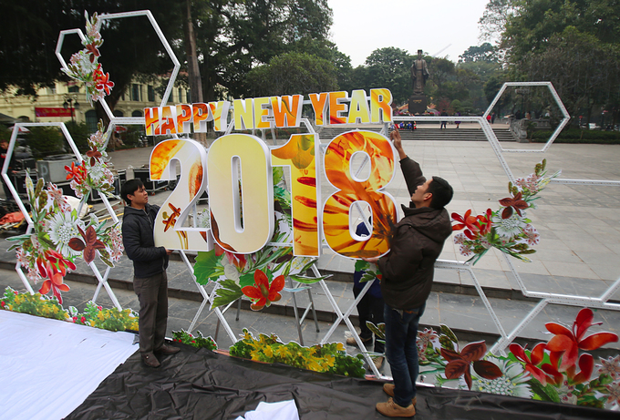 Men put up a Happy New Year banner at Ly Thai To Park  in Hanoi. Vietnam joined the world to celebrate the start of 2018 more  than a month ago, but the anticipation is high once again, or even  higher, now that the country is counting down to the Lunar New Year,  which begins next Friday and is known among the Vietnamese as Tet.