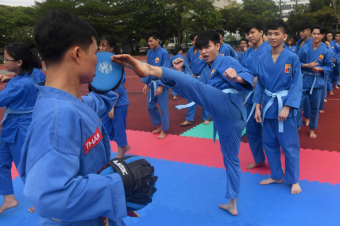 Students from the IVS practice vovinam with an instructor (L) at the campus in Ho Chi Minh City.