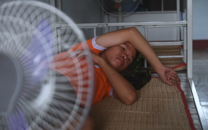 A srudent rests on his bed inside the dormitory after lunch on the campus in Ho Chi Minh City.