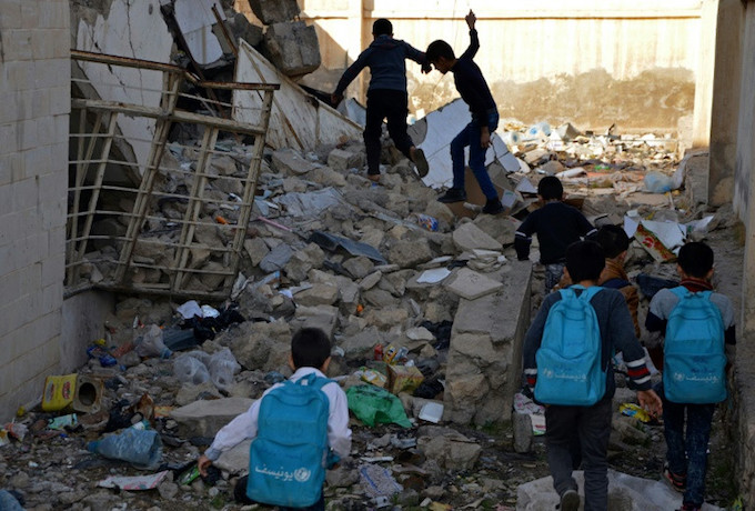 Iraqi children walk in rubble as they head to school in the battered city of Mosul on December 27, 2017