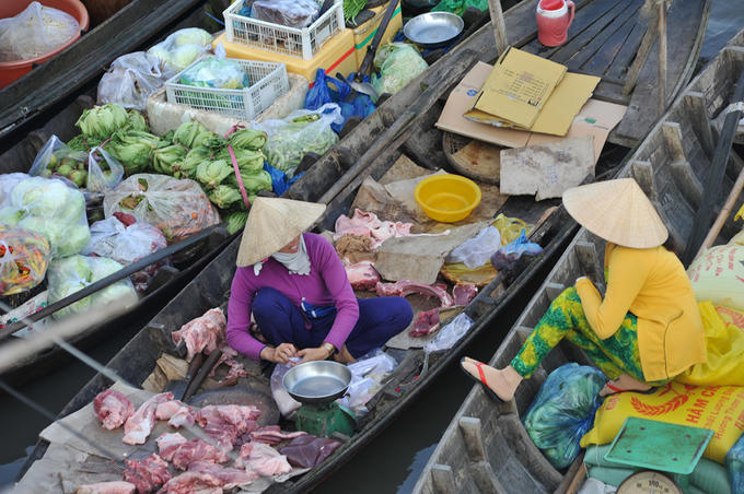 A woman sells pork next to a boat of cabbage and red  chili. Braised pork with eggs (thit kho tau) is a popular Tet dish in  southern Vietnam.