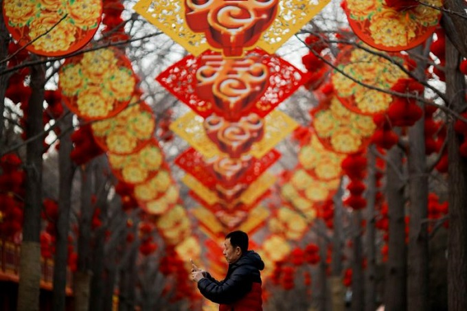 A man takes pictures of trees decorated for Spring Festival ahead of the Chinese Lunar New Year at Ditan Park in Beijing, China, February 11, 2018. Photo by Reuters/Thomas Peter