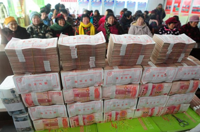 Villagers wait to collect their share of bonuses at a ceremony by an agricultural cooperation, ahead of the Chinese Lunar New Year, or Spring Festival, in Fuyang, Anhui province, China, January 31, 2018. Photo by China Daily via Reuters