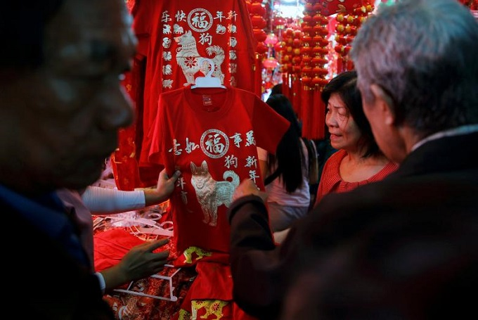 A person holds a T-shirt for the upcoming Chinese Lunar New Year of the Dog at Glodok market in Jakarta,  Indonesia, February 13, 2018. Photo by Reuters/Beawiharta