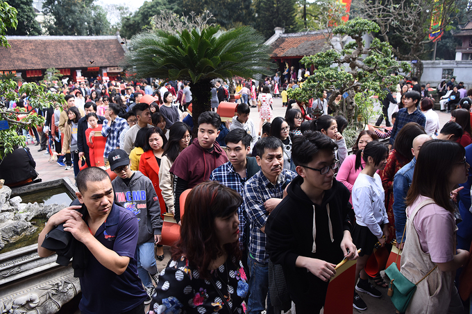 People stand in a queue spanning a few hundred meters to get blessings in calligraphy on red or yellow do paper priced at VND 80,000 ($3.53) per sheet.