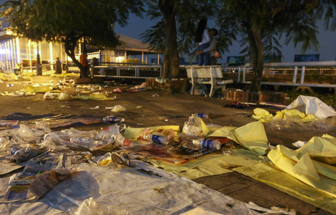 Newspapers, cardboards, plastic bags are seen left behind by spectators who used them to cover the ground while sitting to watch fireworks by the river.