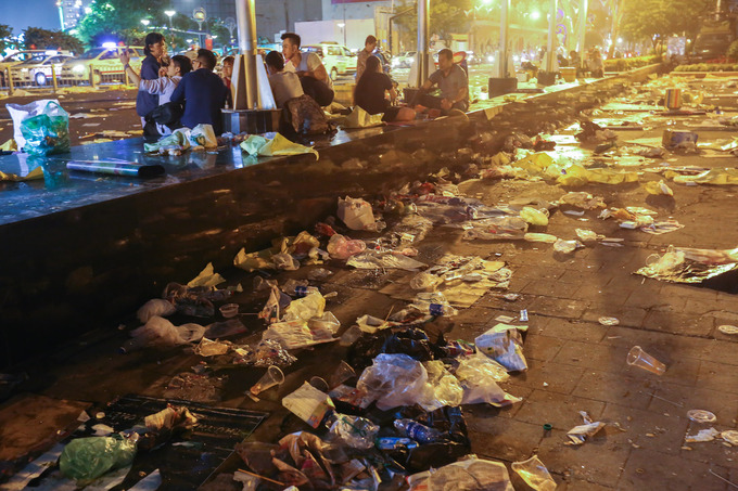 Young people eat and joke in the sea of rubbish on Ton Duc Thang Street at dawn on the first day the Year of the Dog (Feb. 16).