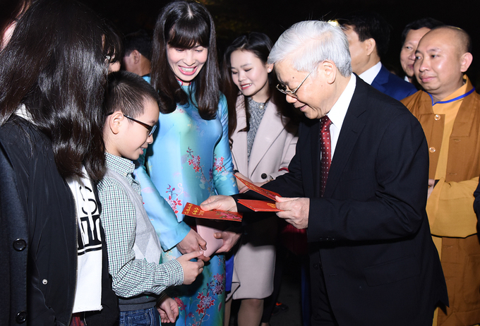 The Party leader gives li xi, lucky money to children, who are welcoming the New Year with their families around Sword lake.