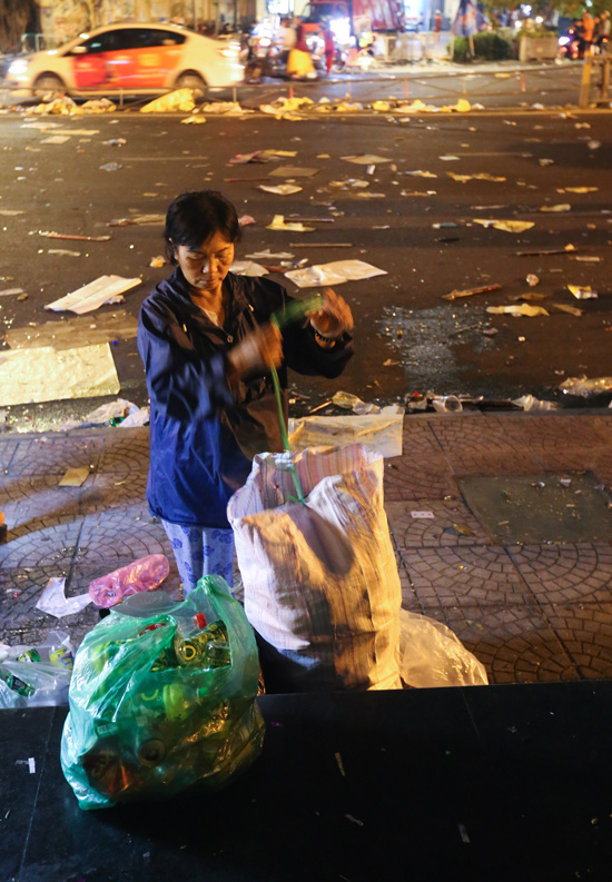 A scrap collector is seen picking up bottles.