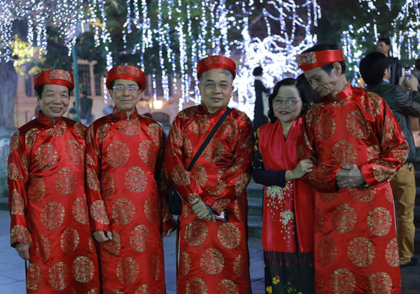 A group of elderly men in traditional ao dai prepare for an offering ceremony at the statue of Emperor Ly Thai To by the lake.