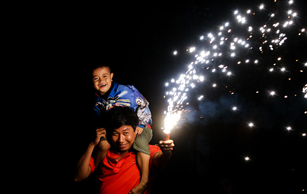 A man carries his son on his shoulders as he lights up a flare to celebrate the new lunar year.