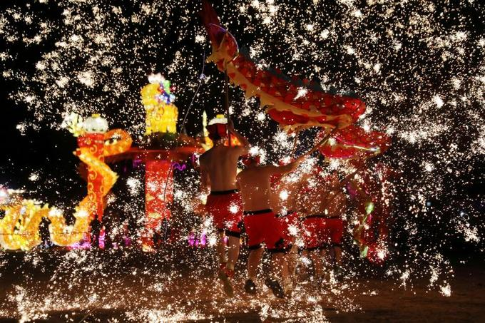 Folk artists perform  a fire dragon dance under a shower of sparks from molten iron in  Shangqiu, Henan province, China, February 14, 2018. Photo by Reuters/Stringer