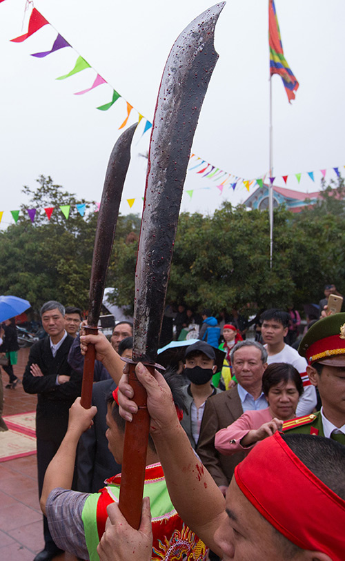 After the ceremony, the two executioners held their bloodstained swords up high while surrounded by police officers to prevent people from trying to soak their money with the blood.