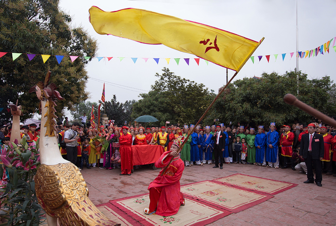 Near noon, the signal flag is waved to mark the beginning of the pig slaughter ceremony.