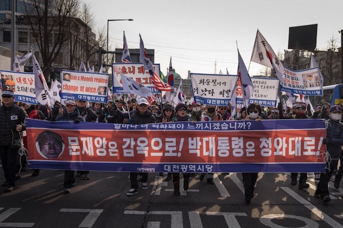 Anti-North Korean protesters march during a rally against an upcoming visit by Kim Yong Chol who will head an eight-member delegation at the Pyeongchang Winter Olympic Games closing ceremony, in Seoul on February 24, 2018. Angry relatives of sailors killed in the 2010 sinking of a South Korean warship protested against the impending visit to the Winter Olympics of a North Korean general blamed for the attack. Photo by AFP/Joseph Chung